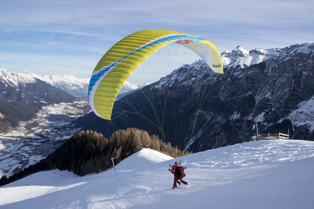Paraglider starten auf der Skipiste